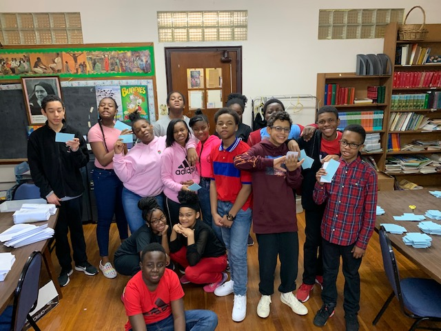 Students from 7th grade posing with raffle tickets