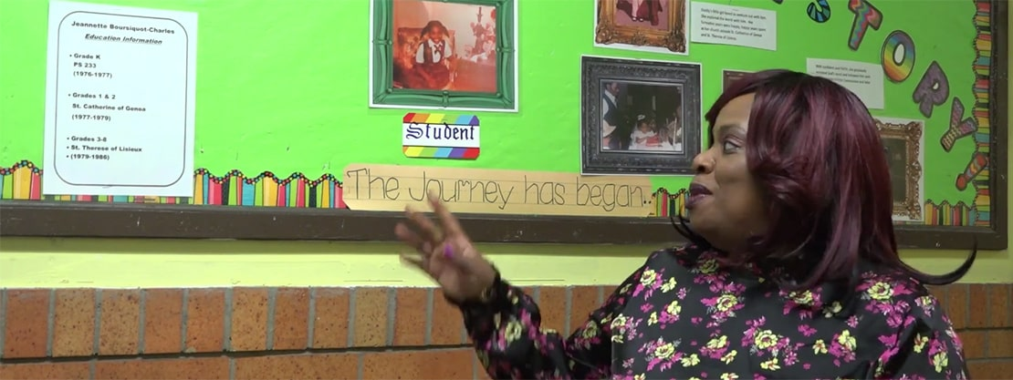 Mrs. Charles in front of bulletin board with picture of her as student